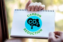 Hand drawing carbon reduction concept on a notepad