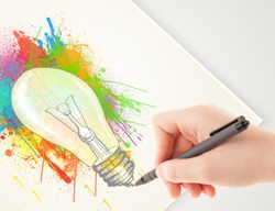 Hand drawing colorful idea light bulb with a pen on paper