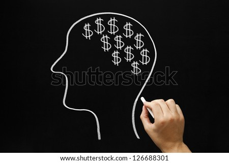 Hand drawing Human head and many dollar signs with white chalk on blackboard.