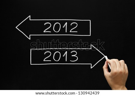 Hand drawing New year concept with white chalk on a blackboard. Going ahead to year 2013 and leaving the year 2012 behind.