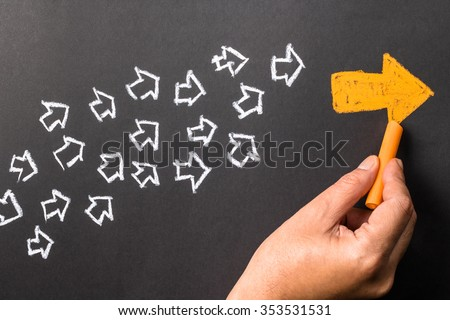 Hand drawing orange arrow as trend leader with many white arrows as follower