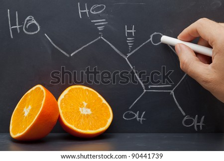 Hand drawing structural formula of vitamin C on blackboard with oranges in front
