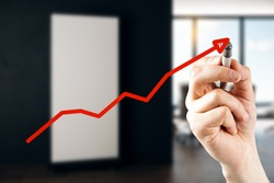 Hand drawing upward red economic arrow on blurry office interior background. Growth and increase concept. Multiexposure