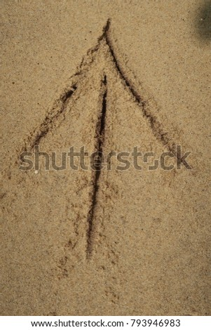 Hand drawn arrow in the ocean sand beach. #793946983