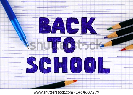 Hand drawn doodles message Back to School on checkered paper with blue ballpoint pen and pencils. #1464687299