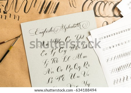 Hand drawn latin calligraphy of brush script. Letters of the alphabet written with a paint brush. Calligraphy, hobby, education concept. top view, flat lay. #634188494