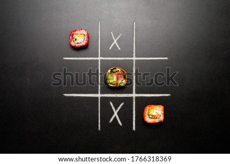 Hand drawn Tic Tac Toe game with Japanese sushi roll pieces instead zero on dark chalkboard background. Asian rolls with salmon, snow crab, avocado and healthy roll with cucumber instead rice.