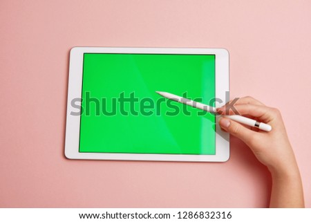 hand draws a pencil on a tablet with a chromakey on the screen