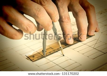 hand draws a pencil on the drawing