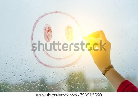 Hand draws a positive funny smiley on a rainy autumn window