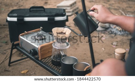 Hand drip coffee in the camp, A man pouring water on coffee ground with filter.Drip coffee and camping.