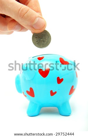 hand dropping coin in piggy bank