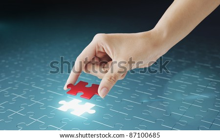 Hand embed missing puzzle piece into place. Business concept for completing the final puzzle place