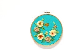 Hand embroidery of floral ornament with woolen threads on green canvas. The flowers are embroidered with punched tapestry or carpet seam, leaves are with tambour or chain stitch. Flat lay, copy space