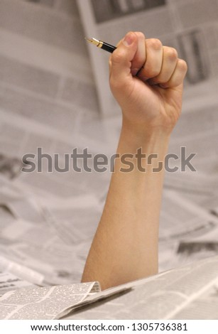 hand emerging from the pages of newspapers