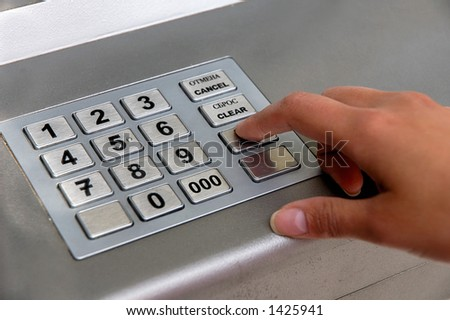 Hand entering personal identification number on ATM dial panel