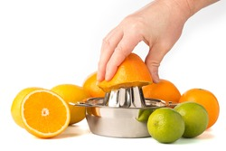 Hand extracting an orange in stainless steel citrus juicer surrounded by whole citrus fruits.