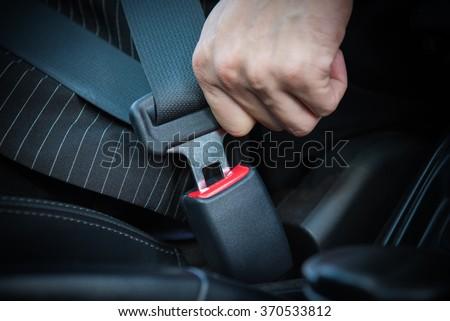 Shutterstock Hand fastening seat belt in the car