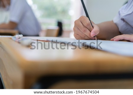 Hand female Asian students taking exam test and concentration reading document exercise at classroom in high school. Teenager notes for SAT PISA measurement educational, back to school for evaluation Stok fotoğraf ©