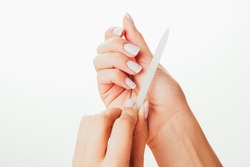 Hand filing nails with glass nail file on the white background