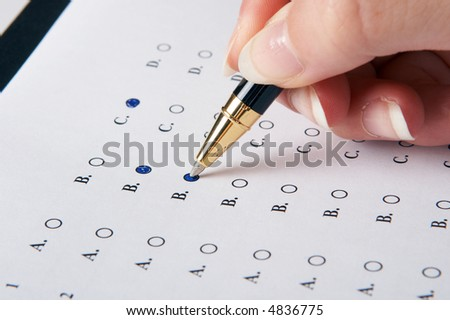 Hand filling in an evaluation form with a pen