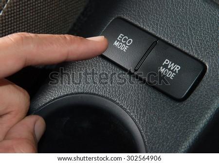 Hand finger press button Eco mode in car,Green concept.