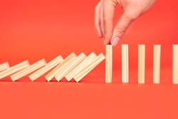 hand finger stops falling wooden dominoes, red background, domino principle, business concept.