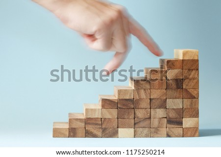 hand finger walk on stacked wooden block like stairs. rises on the steps. Business development and growth concept. #1175250214