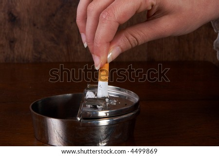 Hand finishing a cigarette in an ashtray