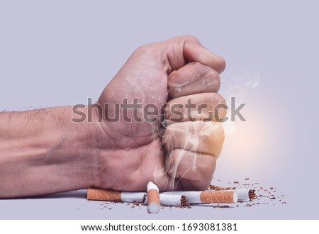 Hand fist smash or punch on cigarette.Cigarettes is addictive to be cancer.smoking reduction campaign in World No Tobacco Day.
