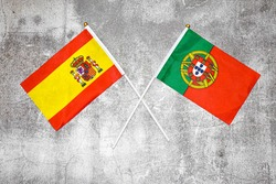 Hand flags of Spain and Portugal on Abstract background