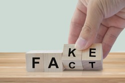 Hand flip wood cube change the word Fact or Fake. April fools day concept.