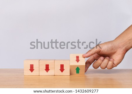 Hand flip wooden cube with down arrow to arrow pointing up on white background. Concept of growth and success or rising successful development and business development in the future #1432609277