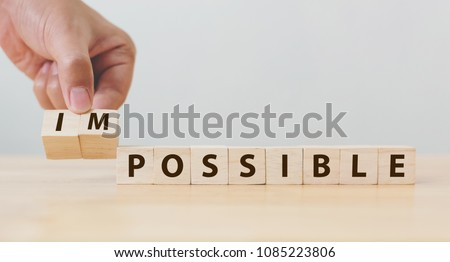 Hand flip wooden cube with word impossible to possible, Personal development and career growth or change yourself concept