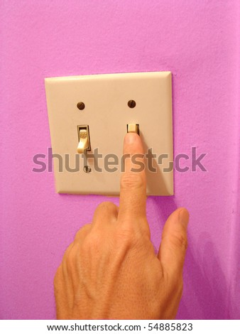hand flipping light switch with pink wall