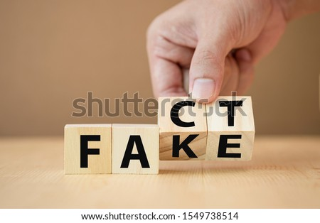 Hand flipping wooden cubes for change wording from 'fake' to 'fact'. Photo stock ©