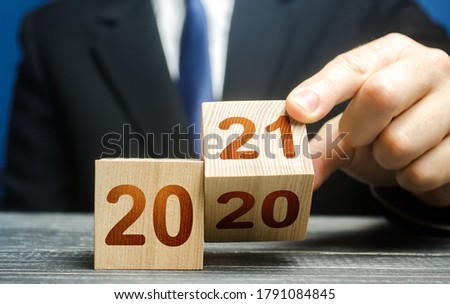 Hand flips a block changing 2020 to 2021. New year beginning. Holidays and Christmas. Trends and changes in the World. Summing work done. Keep up with everything planned. Build plans. New normal.
