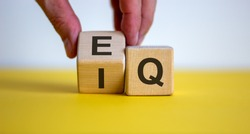 Hand flips a cube and changes the expression 'IQ' to 'EQ'. Beautiful yellow table, white background. Concept of emotional and  intelligence quotient. Copy space.
