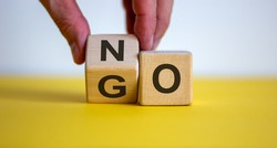 Hand flips a cube and changes the word 'no' to 'go'. Beautiful yellow table, white background. Concept. Copy space.