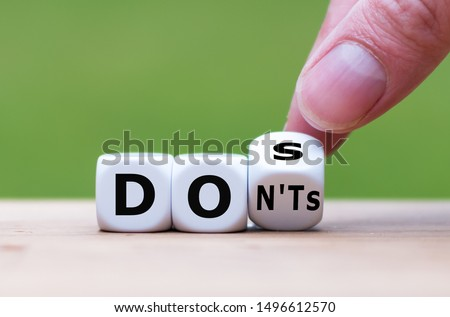 Hand flips a dice and changes the expression 'don'ts' to 'does' Foto stock ©