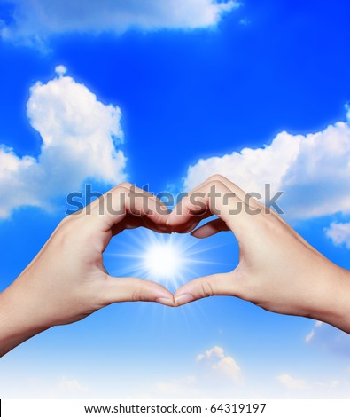 hand forming a heart with blue sky - stock photo
