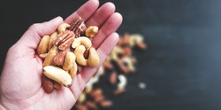 Hand Full of Mixed Nuts Over More Nuts in the Background on Black Table. Selective Focus on Hand. Top View.