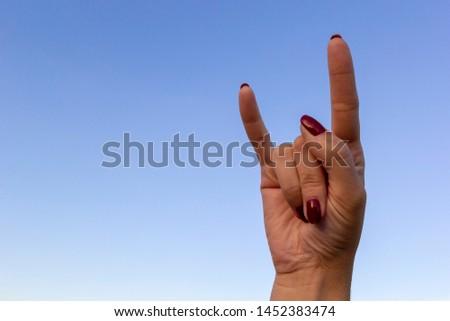 Hand gesturing rock & roll, heavy metal, devil horns gesture or I love you on blue sky background #1452383474