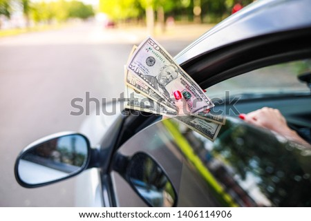 hand girl gives dollars through the glass of the car