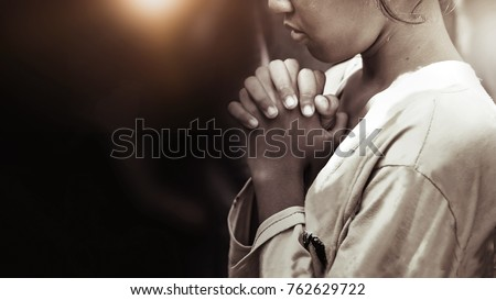 Hand girl praying in the church in vintage tone, Hands folded in prayer concept for faith, spirituality and religion