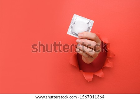 Hand give condom on torn red paper wall. Safe pleasure and protection, contraception, protection from AIDS and day to fight AIDS. Copy space aside for your advertising content