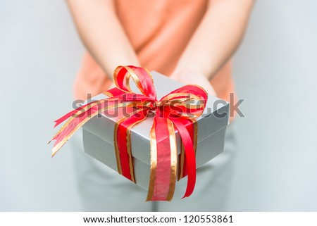 hand give silver gift box with red and gold ribbon