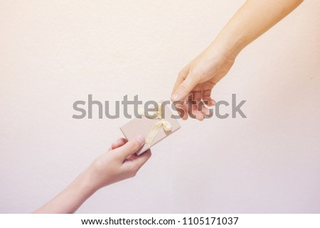 Hand gives a gift to female with copy space background.
