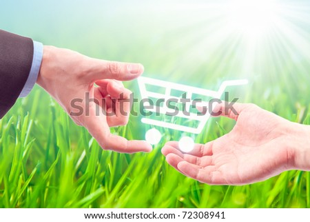 Hand gives a shopping cart on the nature background - stock photo