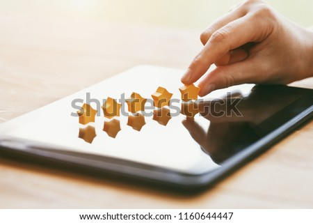hand gives five stars rating as product feedback with tablet computer